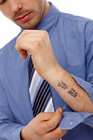 tattoo face: Young businessman unbuttoning shirt, showing small tattoo in forearm. Stock Photo