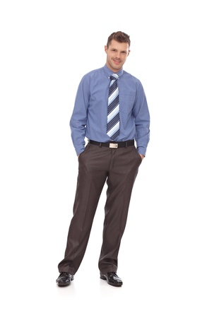 stubbly: Confident young businessman standing with hands in pockets, smiling. Full-length. Stock Photo