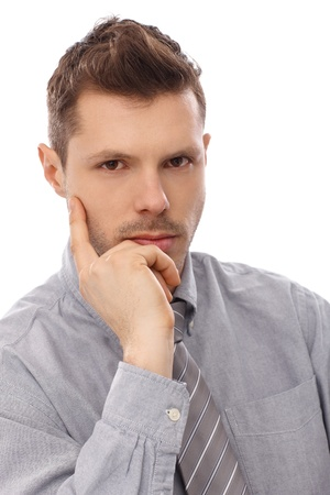 Closeup portrait of serious young businessman, thinking. photo
