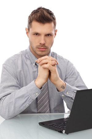 Serious looking young businessman sitting at desk, using laptop computer. photo