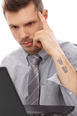 Trendy businessman with tattoo working on laptop computer. photo