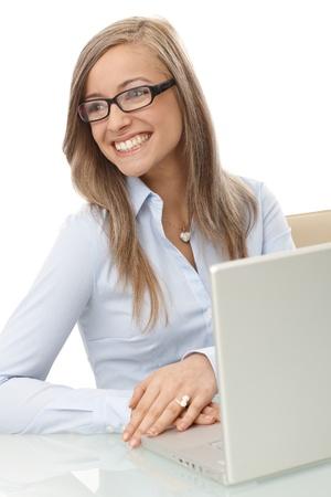 Portrait of smiling blond businesswoman sitting at desk, having laptop computer. photo
