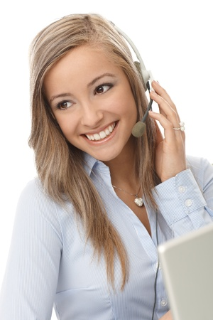 customer service representative: Portrait of happy young customer service representative, using headphones. Stock Photo