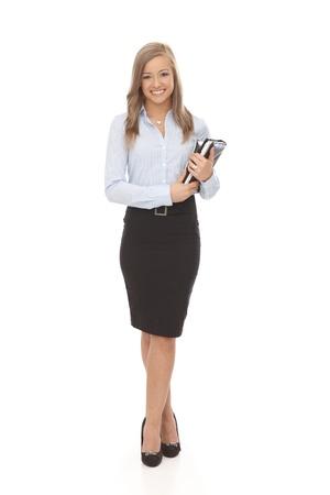 full size: Pretty secretary holding personal organizer, smiling. Full size.