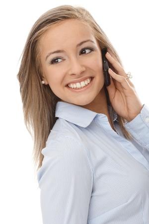 Beautiful blonde woman talking on mobile phone, smiling, looking away. photo
