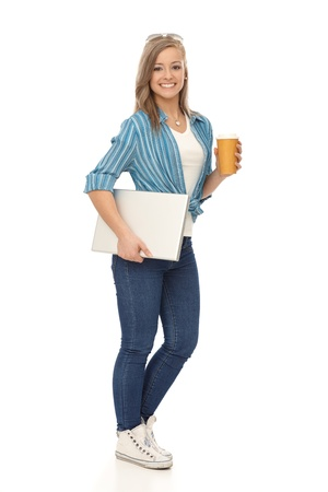 Full size young blonde woman walking with laptop and coffee, smiling. photo