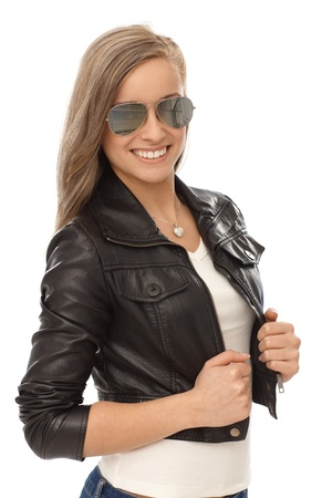 bata blanca: Chica rubia de moda sonriendo en chaqueta de cuero y gafas de sol. Foto de archivo