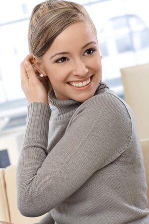 Portrait of happy young woman smiling, stroking hair behind ears. photo
