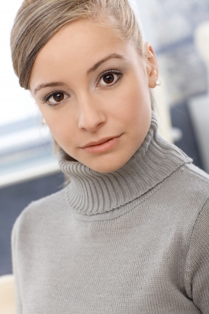 turtleneck: Closeup portrait of young blonde girl, looking at camera.