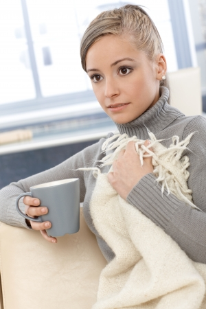 turtleneck: Young woman resting at home, drinking tea, covered by blanket.
