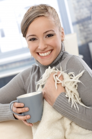 turtleneck: Beautiful young woman smiling, drinking tea, covered by blanket at home.