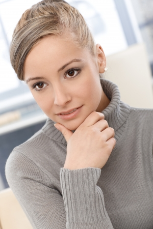 Closeup portrait of attractive young woman in grey pullover. Stock Photo - 13964837