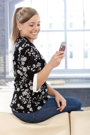 Happy young girl using mobile phone at home, sitting on back of sofa, smiling. photo