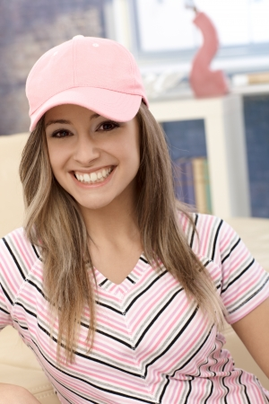 baseball cap: Sporty girl smiling in pink baseball cap at home.