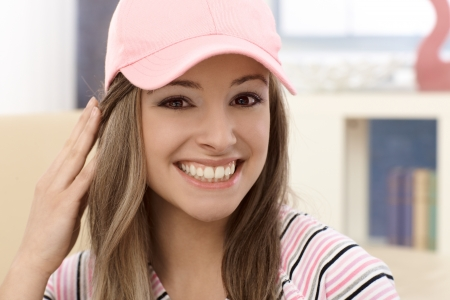 Closeup portrait of attractive young girl in pink baseball cap, smiling. photo
