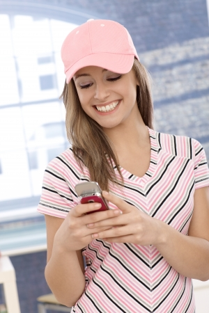 Casual girl in pink baseball cap using cellphone, smiling. photo