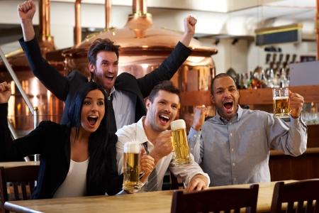 hombre tomando cerveza: Amigos felices en pub ver deportes en la televisión juntos bebiendo cerveza vítores para el equipo y celebrar.
