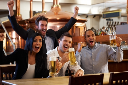 friends happy: Happy friends in pub watching sport in TV together drinking beer cheering for team and celebrating.
