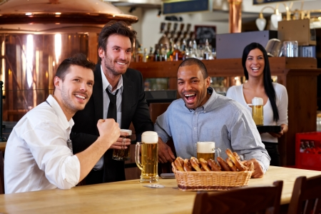 horizontal bar: Happy friends having leisure in pub watching sport in TV together drinking beer cheering for team. Stock Photo