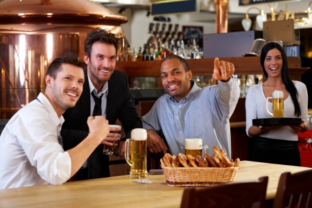 Happy friends having leisure in pub watching sport in TV together drinking beer cheering for team. Stock Photo - 13964791