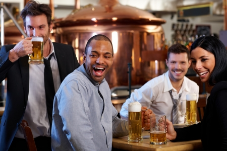 beer in bar: Happy friends having fun in pub watching sport in TV together drinking beer cheering for team. Stock Photo