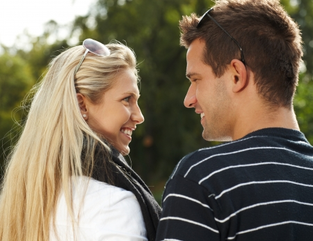 other side of: Young couple smiling, looking at each other in park, view from behind.