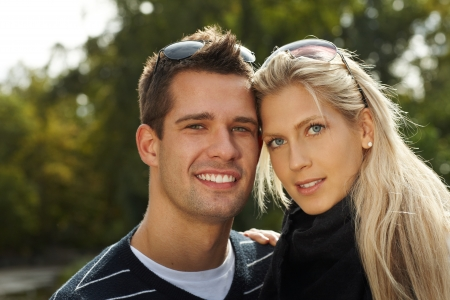 amigos abrazandose: Retrato de una pareja joven y atractiva en el parque, sonriendo.