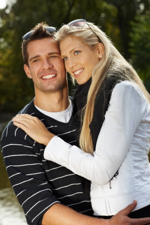 amigos abrazandose: Atractivo joven pareja de enamorados abrazándose en el parque, sonriendo.
