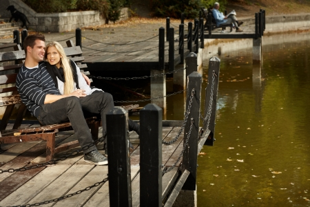 Attractive couple sitting on bench in park at autumn, enjoying sunshine. photo