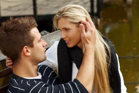 Giovane coppia seduta sulla panchina di lago, baciare.