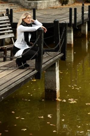 en cuclillas: Atractiva chica en cuclillas al lado del lago en el parque en otoño.