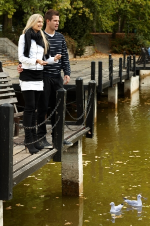Young couple standing by lake at autumn, throwing pebbles to water. photo