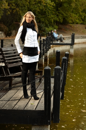 Pretty blonde girl standing by lake in autumn. photo