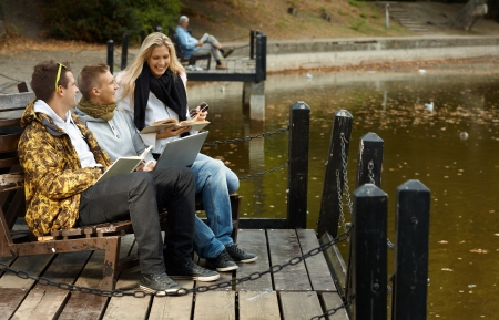 Young friends studying by lake, having fun, smiling at autumn. photo