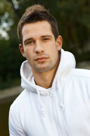 bristly: Outdoor portrait of young man in park, looking at camera.