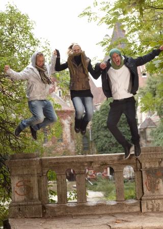 compa�erismo: El compa�erismo de j�venes se divierten en el parque de oto�o, saltar.