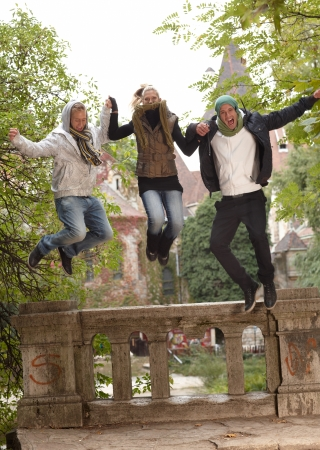 Young companionship having autumn fun in park, jumping. photo