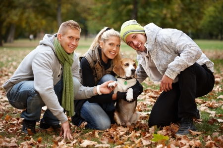 Young friends with cute dog smiling in park at autumn. photo