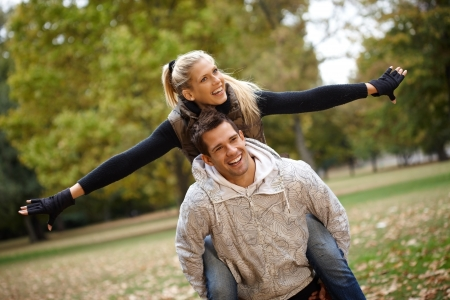 Attractive young couple having fun in autumn park, boy carrying girl piggyback. photo