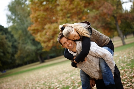 man carrying woman: Attractive loving couple having fun in autumn park, laughing, piggyback. Stock Photo