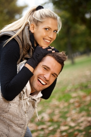 Autumn portrait of beautiful young smiling couple having fun in park. photo