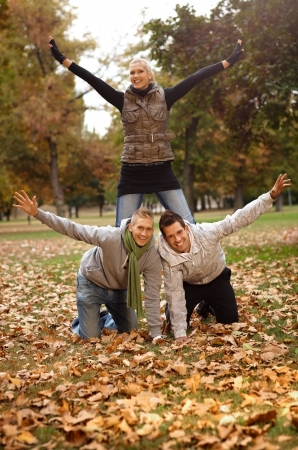 outspreading: Happy young friends having fun in autumn park, girl kneeling on boys back. Stock Photo