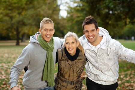 Attractive young friends having fun in autumn park, smiling, looking at camera. photo