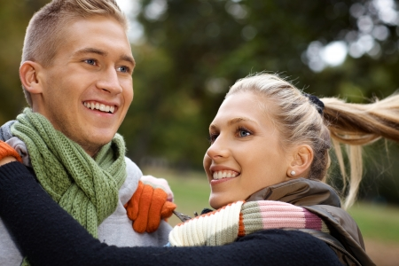 Attractive young couple having fun in park, smiling. photo