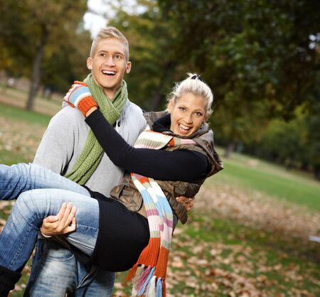 Attractive young couple having autumn fun in park, laughing. photo