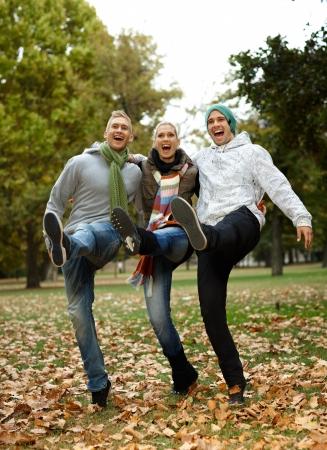 amigos abrazandose: Feliz j�venes amigos divirti�ndose en el parque, riendo. Foto de archivo