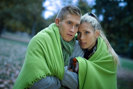 Young couple feeling cold in gloomy autumn park, covered by blanket, cuddling. photo