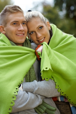 huddling: Smiling young couple on cold autumn day, covered by blanket.