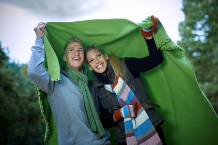 huddling: Young couple smiling under blanket in rainy autumn park. Stock Photo