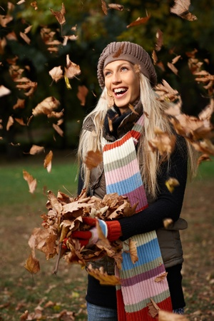 Beautiful young girl having fun in autumn park, laughing with autumn leaves in hand. photo